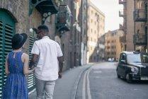 Jeune couple marchant le long de la rue — Photo de stock