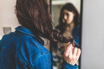 Giovane donna in piedi davanti al mirro — Foto stock