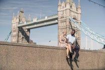 Giovane coppia seduta sul muro — Foto stock