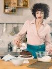Жінка прикрашати шоколадний торт — стокове фото