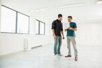 Männer stehen im leeren Büroflächen — Stockfoto