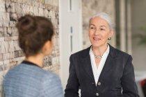 Взрослые деловые женщины разговаривают в офисе — стоковое фото
