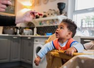 Baby boy in highchair being fed — Stock Photo