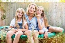 Mère et filles assis sur trampoline — Photo de stock