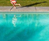 Мальчик, завернутый в полотенце, бегущий у бассейна — стоковое фото