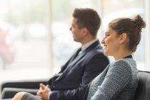 Businessman and woman sitting on sofa — Stock Photo