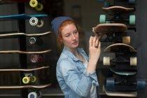 Woman working in skateboard shop — Stock Photo