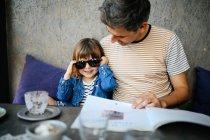Menina brincando com pais óculos de sol — Fotografia de Stock