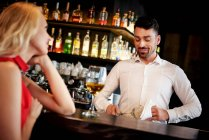 Barman flirting with young woman — Stock Photo