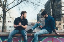 Male hipsters sitting on wall looking at smartphone — Stock Photo