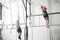 Couple rope climbing in gym — Stock Photo