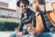 Hipster seduti a parete con smartphone — Foto stock