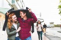 Couple walking outdoors in rain — Stock Photo