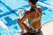 Nageur, assis à l'extrémité de la piscine — Photo de stock