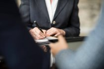Empresária e homem fazendo anotações — Fotografia de Stock