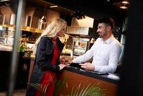 Торкаючись молоді жінки руку офіціант — стокове фото