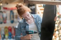 Woman working in skateboard shop — Stock Photo