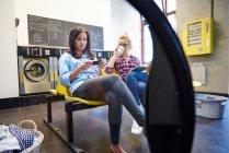 Due donne che si siedono in lavanderia a gettoni — Foto stock