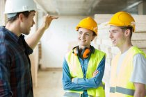 Three people standing in constructions site — Stock Photo