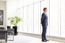 Confident businessman looking through window — Stock Photo