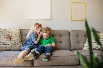 Девушка на диване шепчет брату: — стоковое фото