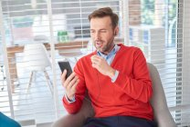Man wearing earbuds looking at smartphone — Stock Photo