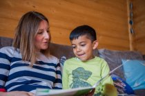 Childminder reading book with boy — Stock Photo