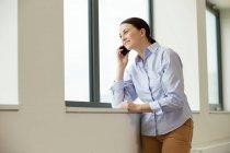 Woman standing beside window — Stock Photo