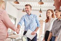 Деловые люди в офисе пожимают руки — стоковое фото