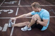 Man sitting on sports track — Stock Photo