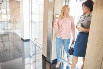 Colegas no prédio de escritórios usando elevador — Fotografia de Stock