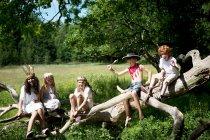Crianças em trajes sentados no tronco da árvore — Fotografia de Stock