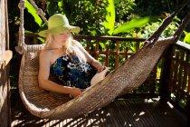 Mujer relajante en hamaca en el porche - foto de stock