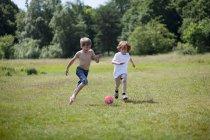 Ragazzi che giocano a calcio nel campo erboso — Foto stock