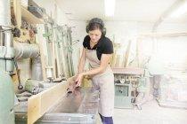 Female carpenter working in workshop — Stock Photo