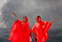 Women in red ponchos waiting for rain — Stock Photo