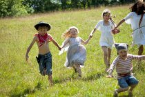 Children in costumes running in field — Stock Photo