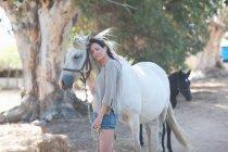 Mujer que se inclina sobre el cuello del caballo - foto de stock