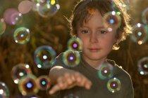 Niño jugando con burbujas al aire libre - foto de stock