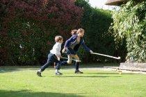 Crianças jogando hóquei no quintal — Fotografia de Stock
