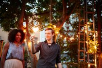 Young man holding sparkler — Stock Photo