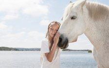 Кінь контактний дівчина на пляжі — стокове фото