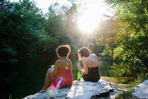 Two women relaxing by river — Stock Photo