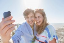 Couple photographing themselves on beach — Stock Photo