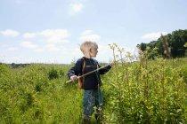 Хлопчик стоїть в полі з метелик нетто — стокове фото