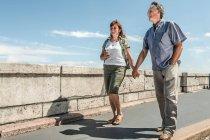 Coppia che si tiene per mano sul ponte — Foto stock