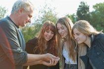 Людина щось запропонувати для дівчат-підлітків — стокове фото