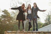 Girls walking on stone wall — Stock Photo