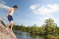 Мальчик, восхождение на скалы, река — стоковое фото
