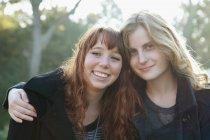 Teenage girls hugging outdoors — Stock Photo